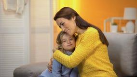 Fêmea bonita de sorriso que abraça a filha pré-escolar maciamente feliz, confiança filme