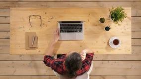 Fêmea bonita do freelancer que levanta e que trabalha na linha com os auriculares com mic em um desktop ou em uma casa do escritó video estoque