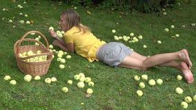 A fêmea bonita na mentira amarela da camisa no gramado e o bocado comem a maçã perto da cesta de vime com frutos 4K video estoque