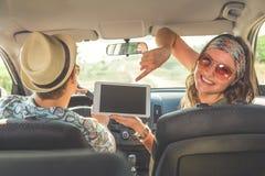 Fêmea bonita que guarda o dispositivo digital da tabuleta e que senta-se no carro com seu noivo Conceitos do curso e da tecnologi imagem de stock royalty free
