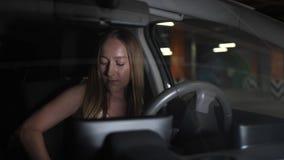 Fêmea bonita que obtém no subterrâneo estacionado carro filme