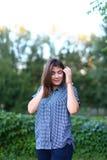A fêmea bonita que olham in camera, o sorriso bonito e corrigem o cabelo Fotos de Stock