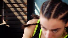 Fêmea branca apta que estica e que aquece os músculos do braço no gym filme