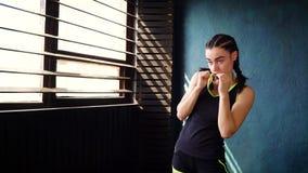 A fêmea branca apta que estica o braço muscles no gym video estoque
