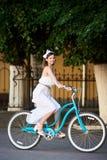 A fêmea brincalhão na bicicleta do vintage está montando ao longo da rua da cidade imagens de stock