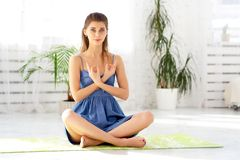 Fêmea calma bonita que medita na pose fácil em casa que senta-se na esteira, guardando as mãos, gesto yogic imagem de stock royalty free