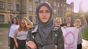 Fêmea caucasiano bonita no hijab que está com mãos cruzadas no meio da demonstração das feministas na rua vídeos de arquivo