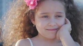 Fêmea caucasiano bonito da criança pequena do retrato, ar livre da criança em um vestido cor-de-rosa com uma flor cor-de-rosa em  video estoque