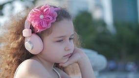 Fêmea caucasiano bonito da criança pequena do retrato, ar livre da criança em um vestido cor-de-rosa com uma flor cor-de-rosa em  vídeos de arquivo