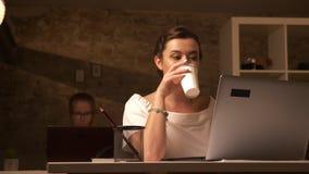 A fêmea caucasiano concentrada feliz está bebendo o café e está olhando o computador ao sentar-se ao lado de seu associado sobre vídeos de arquivo