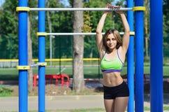 Fêmea caucasiano nova em um sportswear verde-claro inclinado contra a barra horizontal no campo de esportes fotos de stock royalty free