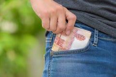 A fêmea colhe o dinheiro do rublo de Rússia do bolso Imagem de Stock