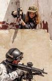 Fêmea com a arma a apontar no soldado Fotos de Stock Royalty Free