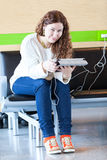 Fêmea com dispositivos electrónicos que passa o tempo Foto de Stock Royalty Free
