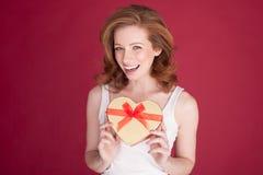 Fêmea com o cabelo vermelho que guarda a forma do coração Fotos de Stock Royalty Free