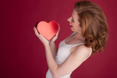 Fêmea com o cabelo vermelho que guarda a forma do coração Imagens de Stock Royalty Free