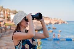 Fêmea com um telescópio no seashore Imagem de Stock