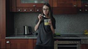 A fêmea com vidros come o café da manhã na cozinha vídeos de arquivo