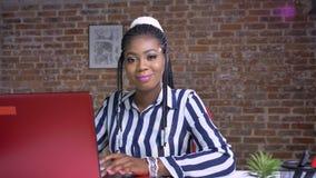 Fêmea consideravelmente africano olhando seu computar e então na câmera feliz e relaxado, sentando-se no escritório do tijolo filme