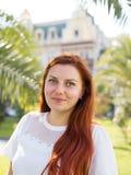 Fêmea consideravelmente atrativa dos jovens com o cabelo vermelho que olha ao redor, andando na rua da cidade tropical com palmei fotografia de stock royalty free