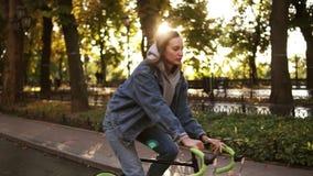 Fêmea consideravelmente caucasiano que monta uma bicicleta no parque ou no bulevar da manhã Opinião lateral uma jovem mulher que  video estoque