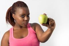Fêmea consideravelmente preta que mostra uma maçã verde. Fotografia de Stock Royalty Free