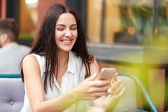 A fêmea contente positiva com expressão alegre, telefone esperto das posses, contente de receber a mensagem no telefone esperto,  imagens de stock