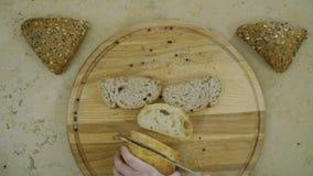 A fêmea corta o pão na placa de corte em slowmotion video estoque