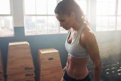 Fêmea da aptidão que toma uma ruptura do exercício intenso no gym imagem de stock