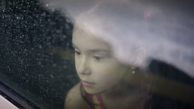 Fêmea da criança no carro em chover