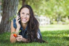 Fêmea da raça misturada que fala no telefone de pilha fora Imagem de Stock