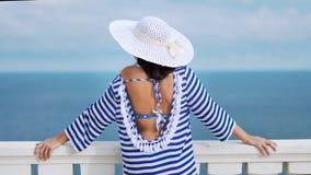 Fêmea da vista traseira no chapéu e nos óculos de sol que estão nas mãos de inclinação do terraço em trilhos brancos antigos video estoque