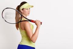 A fêmea de cabelos compridos atlética bonita olha de lado, guardando a raquete de tênis, pondo a sobre o ombro, tampão vestindo d fotos de stock