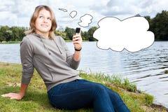 Mulher de pensamento nova com telemóvel Fotografia de Stock