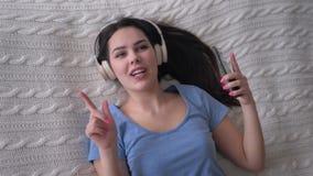 A fêmea de sorriso agradável em fones de ouvido com telefone toma a música do prazer e canta-a ao relaxar no close up da cama  filme