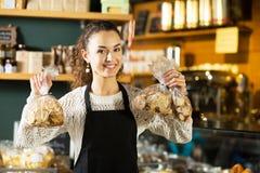 Fêmea de sorriso no avental que vende galdérias imagens de stock