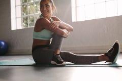 Fêmea de sorriso no gym que toma uma ruptura do exercício fotos de stock