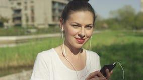 Fêmea de sorriso nos fones de ouvido com smartphone video estoque