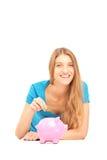 Fêmea de sorriso que pôr uma moeda em um mealheiro Fotos de Stock Royalty Free