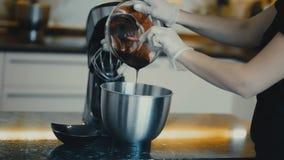 A fêmea derrama de um xarope doce da bacia transparente em amassadeiras de uma bacia video estoque
