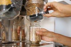 A fêmea derrama lentilhas verdes da máquina de venda automática em um frasco de vidro Compra nova da mulher do vegetariano na loj imagens de stock royalty free
