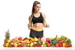 Fêmea desportiva nova com uma corda de salto em torno de sua posição do pescoço atrás de uma pilha das frutas e legumes fotografia de stock