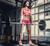Fêmea desportiva 'sexy' no sportswear cor-de-rosa que guarda o barbell fotografia de stock