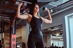 Fêmea desportivo loura no sportswear que faz o exercício em ombros com pesos no clube ou no gym de aptidão imagem de stock