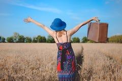 Fêmea despreocupada nos sundress e na terra arrendada do chapéu de jogador Imagem de Stock