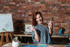 A fêmea do alívio de tensão da terapia da arte estende o pincel fotografia de stock