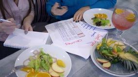 Fêmea do emagrecimento com o calendário do planeamento da dieta para fazer calorias da contagem na folha de papel durante o tempo filme