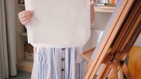 Fêmea do estúdio da arte que prepara a armação da lona de pintura filme