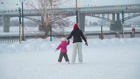 Fêmea e menina que guardam a patinagem no gelo do quando das mãos video estoque