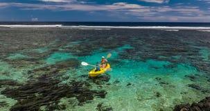 Fêmea e rapaz pequeno que remam a canoa em uma lagoa tropical filme